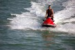 boy on a red  jet ski