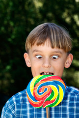 cross eyed boy eating lollipop