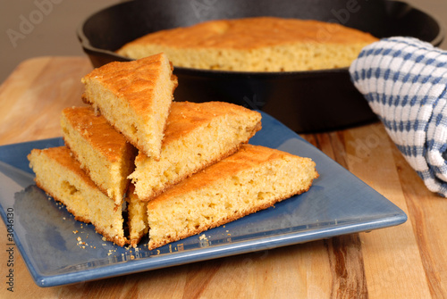 Poster Brood stack of cornbread on a blue plate with skillet in background
