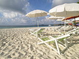 chairs and parasols on the beach poster