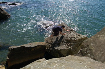 climbing the rocks at the beach