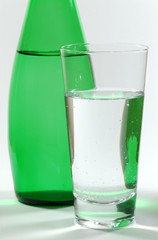 glass of mineral water and green bottle