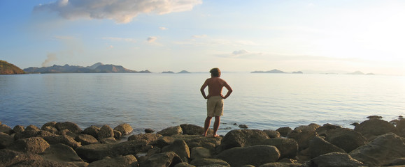 a man looking over the infinite tropical sea and island archipel