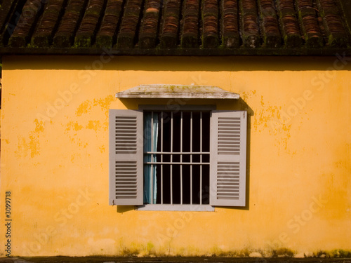 shuttered window in yellow wall