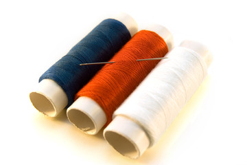 blue, red and white threads with needle