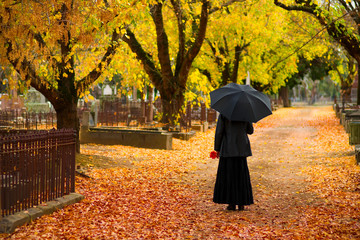 woman in mourning at cemetery in fall