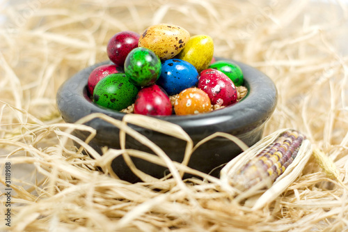 colorful eggs in bowl in straw