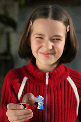 Young gril is holding chocolate egg at easter