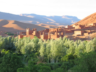moutain with sand dunes and a fortress in an oasis on the foregr