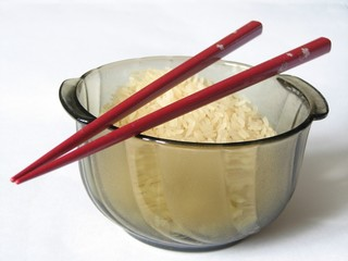 bowl full of uncooked rice with red chopsticks