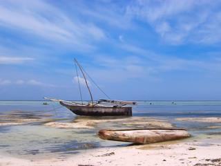 african boat on a tropical beach, zanzibar, tanzania