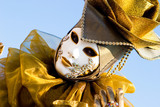 a venetian in a gold costume with a white mask poster