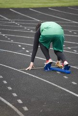 girl track star getting into the starting blocks