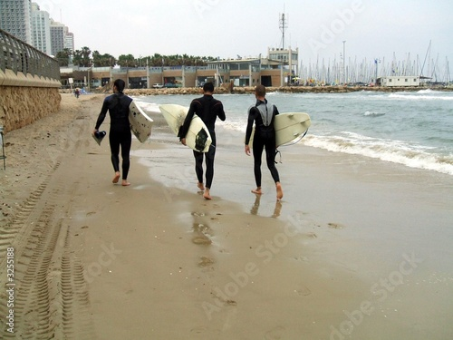 poster of men walking on the beach carrying surf boards