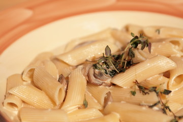 pasta with mushrooms on a beige plate