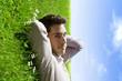 jeune homme sourire détendu herbe et ciel bleu