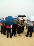 tourists listening to a guide carrying umbrellas poster