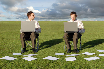 two businessmen on laptops