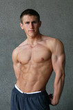 young muscular man showing his muscles poster