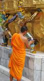 monk inspects a statue at the grand palace, bangkok, thailand - poster