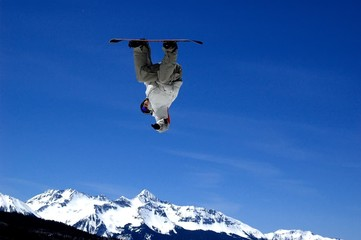 inverted snowboarder flying over a peak