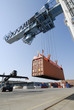 crane lowering container to forklift