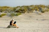 telecommuter on a beach working 3 - 3335161