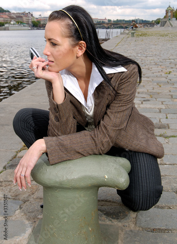 girl with phone at river bank