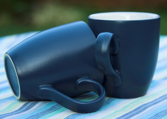 pair of mugs placed on a striped tablecloth
