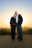 happy mature couple embracing outdoors at sunset poster