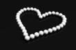 collier coeur perles blanches sur fond noir