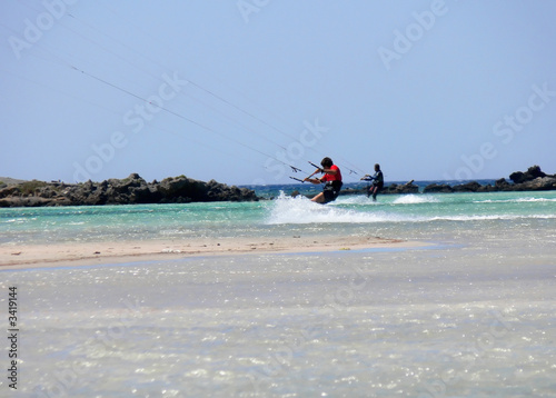 kitesurfers near shore and rocks