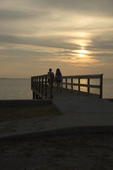 two people on a dock looking at sunset