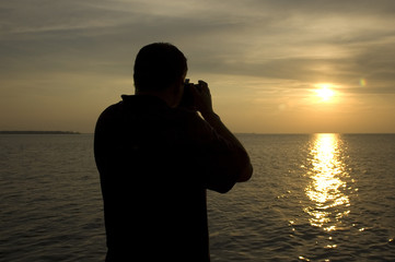 man taking picture of a beautiful sunset