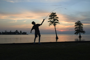young boy fishing in a lake against sunset