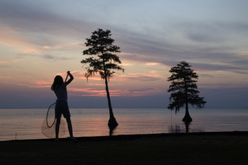 girl catching fish with a net against a beautiful sunset