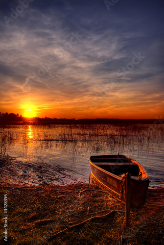 a boat by the lake at sunset - 3428395