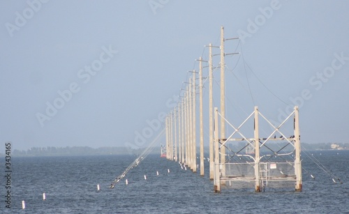 row of power poles over water