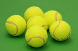 six tennis balls on the green background