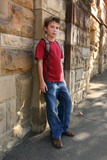 youth leaning against sandstone wall poster