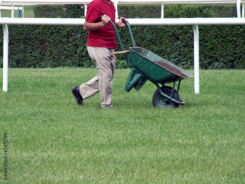 man with wheelbarrow on the field