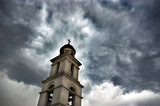 bell tower under dramatic skies poster