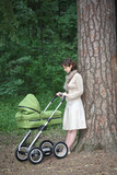 mother with baby carriage in the park poster