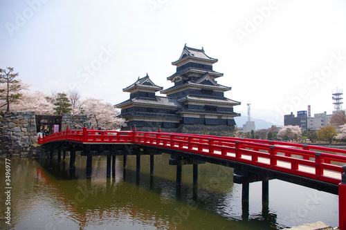 a traditional Japanese castle with red bridge over moat