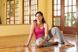 Healthy young woman in gym outfit sitting on the floor poster