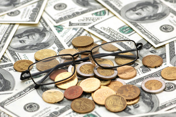 american dollars, reading glasses and various coins