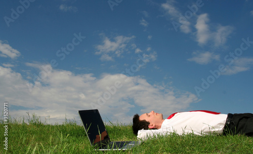man lying on the grass with laptop