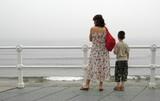 Madre con hijo mirando el mar poster