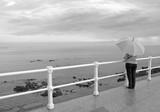 Mujer con paraguas mirando al mar poster
