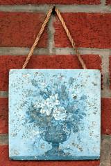 art tile closeup on a red brick wall